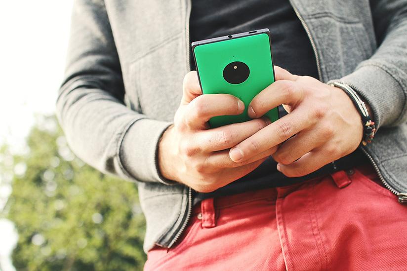Diseño web responsive: Chico mirando una web en móvil.